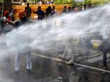 Police charge water canons on BJP workers participating in Jan Raksha Yatra near CPI-M headquarters in New Delhi on Oct 9, 2017.