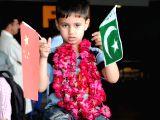 A Pakistani boy evacuated from Yemen holds Chinese and Pakistani national flags at Benazir Bhutto International Airport in Rawalpindi, Pakistan, April 3, 2015. A ...