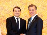 South Korean President Moon Jae-in (R) poses for a photo with Igor Levitin, an aide to Russian President Vladimir Putin and vice president of the Russian Olympic Committee, before meeting a ...