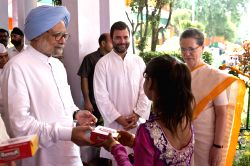 Congress chief Sonia Gandhi, vice president Rahul Gandhi and former prime minister and Congress leader Manmohan Singh distribute sweets to children at AICC headquarters on the occasion of ...