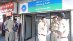 Cooch Behar: Policemen stand outside the SBI ATM centre fem where the teller machine was stolen in Cooch Behar of West Bengal on March 8, 2016.