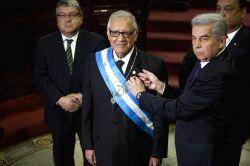 Guatemalan Congress President Luis Rabbe puts the presidential insignias onto new Guatemalan President Alejandro Maldonado during Maldonado's swearing in ...