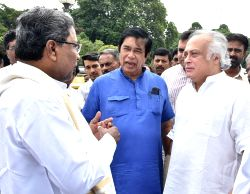 Karnataka Chief Minister Siddaramaiah interacts with Congress Rajya Sabha candidates Jairam Ramesh and Oscar Fernandes at Vidhan Soudha, in Bengaluru, on May 31, 2016.