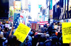 NEW YORK, Feb. 19, 2017 - Protesters hold placards to demonstrate against U.S. President Donald Trump's immigration policy at Times Square in New York City, the United States, on Feb. 19, 2017. About ...