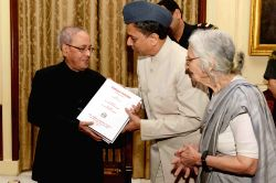 President Pranab Mukherjee receives the first copy of book 'Garuda Purana' (Critical Edition), published by the All India Kashiraj Trust, at Rashtrapati Bhavan, in New Delhi on June 19, ...