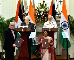 Prime Minister Narendra Modi and Palestine President Mahmoud Abbas witness the exchange of agreements at Hyderabad House in New Delhi on May 16, 2017. Also seen External Affairs Minister ...