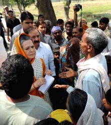 Rae Bareli: Congress president Sonia Gandhi meeting the farmers and their family members at Rae Bareli in Uttar Pradesh who suffered losses due to unseasonal rain on March 28, 2015.