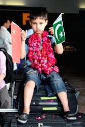 A Pakistani boy evacuated from Yemen holds Chinese and Pakistani national flags at Benazir Bhutto International Airport in Rawalpindi, Pakistan, April 3, 2015. A ...