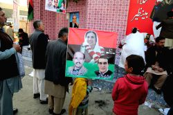RAWALPINDI, Dec. 27, 2016 - A girl holds a portrait of Benazir Bhutto (top) during a ceremony to mark 9th death anniversary at the site where former prime minister Benazir Bhutto was assassinated in ...