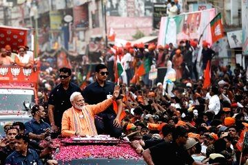 Prime Minister Narendra Modi waves at his supporters during a roadshow ahead of the 2019 Lok Sabha elections, in Varanasi