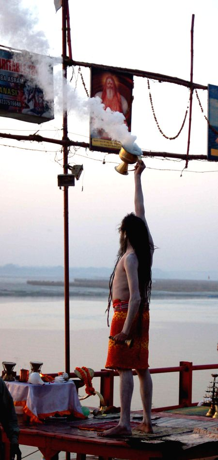 An ascetic performs morning `aarti` on the banks of Ganga river in Varanasi on June 27, 2014.