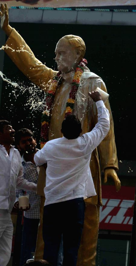 Congress workers wash the Statue of Rajiv Gandhi with milk to staged a protest against the Centre`s decision to name the domestic terminal of Rajiv Gandhi International Airport after ... - N. and T. Rama Rao