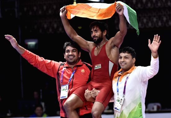 JAKARTA, Aug. 19, 2018 - Bajrang Punia (C) of India celebrates after winning gold medal of Men's Wrestling Freestyle 65 kg Final against Takatani Daichi of Japan in the 18th Asian Games at Jakarta, ...(Image Source: Xinhua/Li He/IANS)