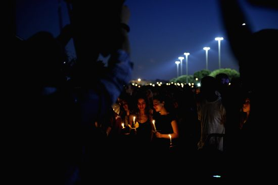 : People hold candles during a vigil for the victims of the shooting at Marjory Stoneman Douglas High School, in Parkland, Florida, the United States, Feb. 15, ...