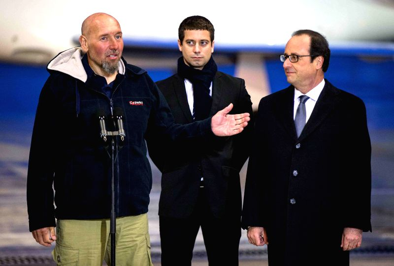 Paris (France): France`s Serge Lazarevic(L) talks with French President Francois Hollande(R) after arriving at Villacoublay`s military airport, west of Paris, Dec. 10, 2014. French Preisdent