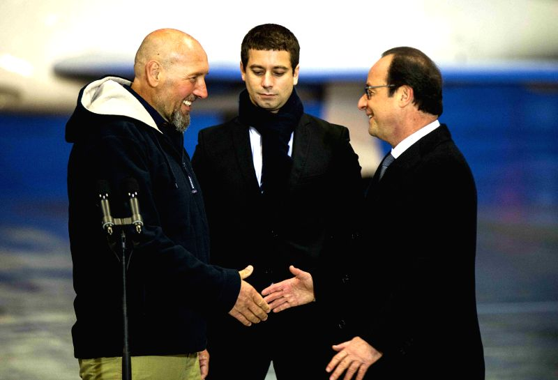 Paris (France): France`s Serge Lazarevic(L) shakes hands with French President Francois Hollande(R) after arriving at Villacoublay`s military airport, west of Paris, Dec. 10, 2014. French ...