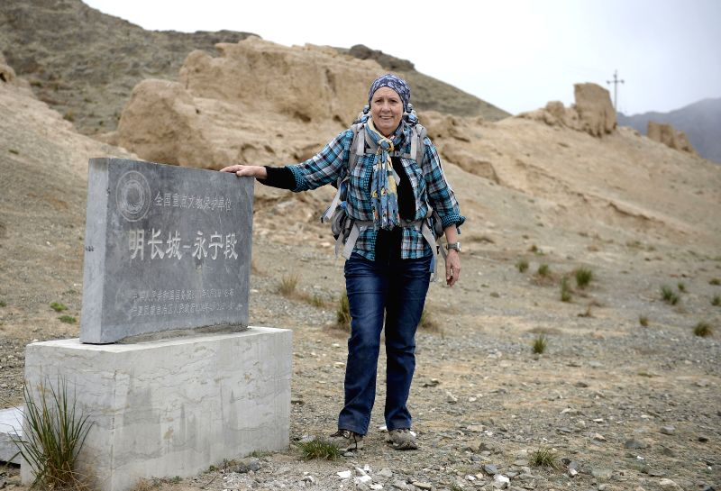 Sylvia poses for photo with a stele as she hiked to the Sanguankou Great Wall of Ming Dynasty (1368-1644) in northwest China's Ningxia Hui Autonomous Region,