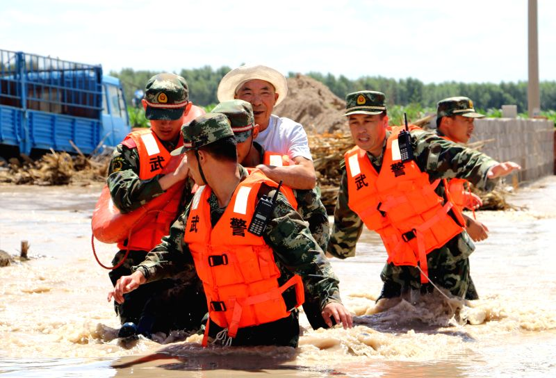 Soldiers of Armed Police Detachment rescue people in Baicheng, northeast China's Jilin Province, July 8, 2014. A total of about 700 flood-stranded ...