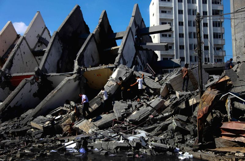 Palestinians inspect the ruins of a destroyed high-rise following Israeli airstrikes in Gaza City, early morning on Tuesday, August 26, 2014. Four huge ...