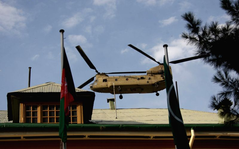A helicopter flies over during a change of command ceremony at the ISAF headquarters in Kabul, Afghanistan on August 26, 2014. U.S. Marine Corps General ..