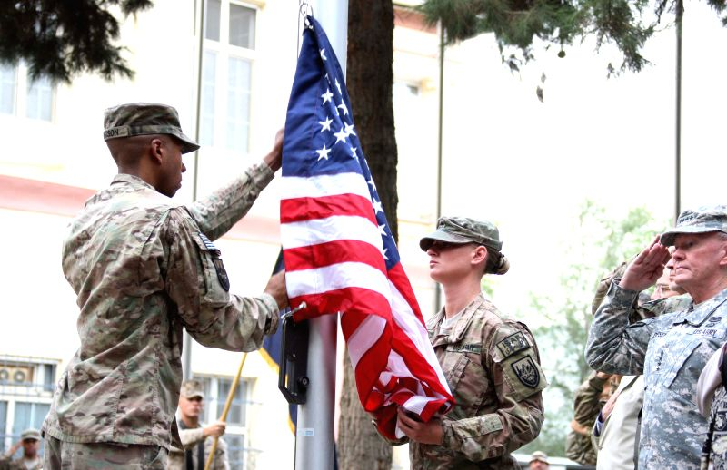 U.S soldiers rise the U.S. flag during a change of command ceremony at the ISAF headquarters in Kabul, Afghanistan on August 26, 2014. U.S. Marine Corps ..