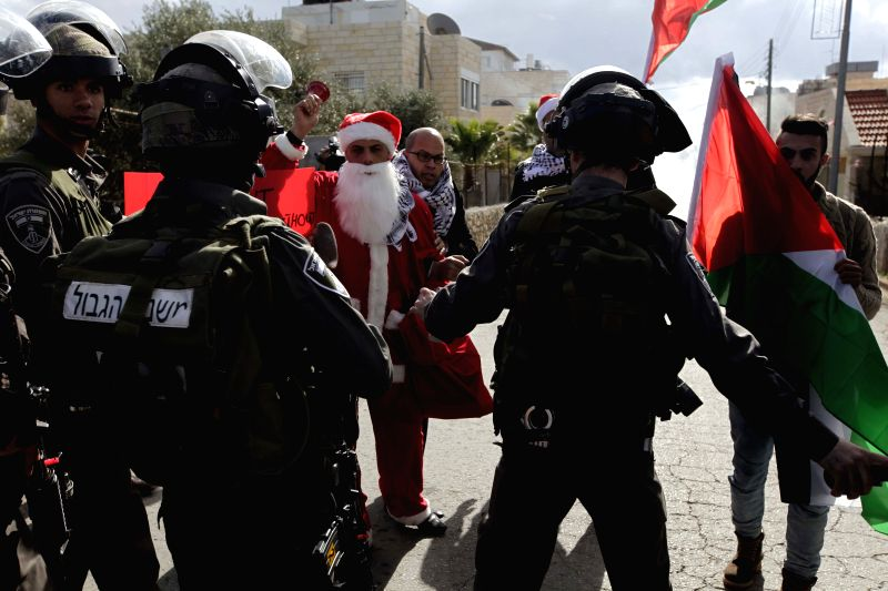Palestinian protesters wearing Santa Claus costumes clash with Israeli soldiers at an Israeli checkpoint in the West Bank city of Bethlehem on Dec. ...