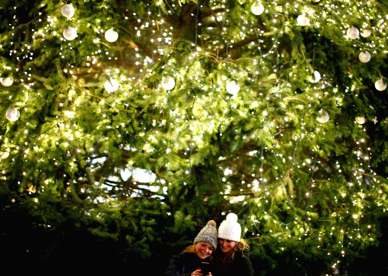 Visitors take photos in front of a Christmas tree decorated with lights in Berlin, Germany, on Dec, 23, 2014.