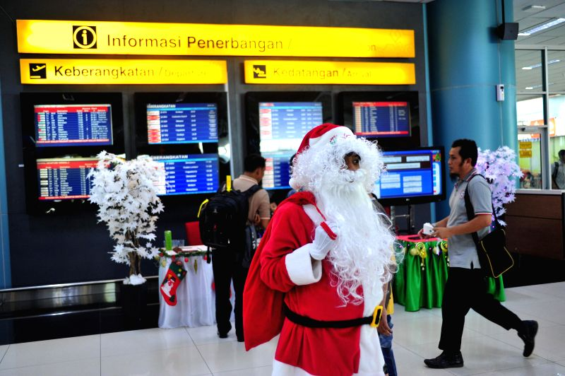 A Santa Claus stands in front of a flight information screen at Terminal 3 of Soekarno-Hatta International Airport in Banten province, Indonesia, Dec. ..