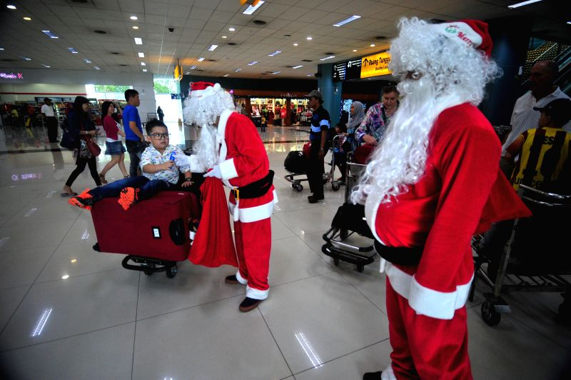 Santa Clauses give presents to passengers at Terminal 3 of Soekarno-Hatta International Airport in Banten province, Indonesia, Dec. 24, 2014. ...