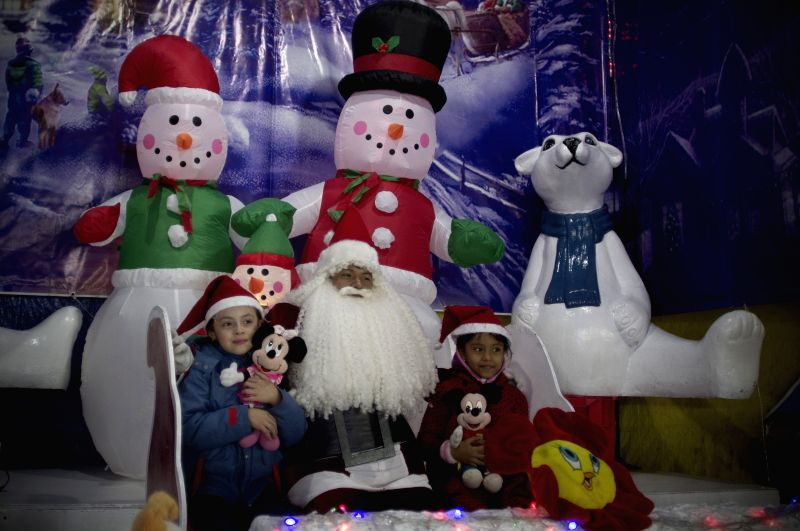 Young student Misael (R), dressed as Santa Claus, poses with children in Mexico City, capital of Mexico, on Dec. 23, 2014. Misael performed as Santa