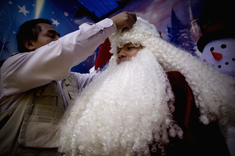 Young student Misael (R) is dressed as Santa Claus in Mexico City, capital of Mexico, on Dec. 23, 2014. Misael performed as Santa Claus to get extra