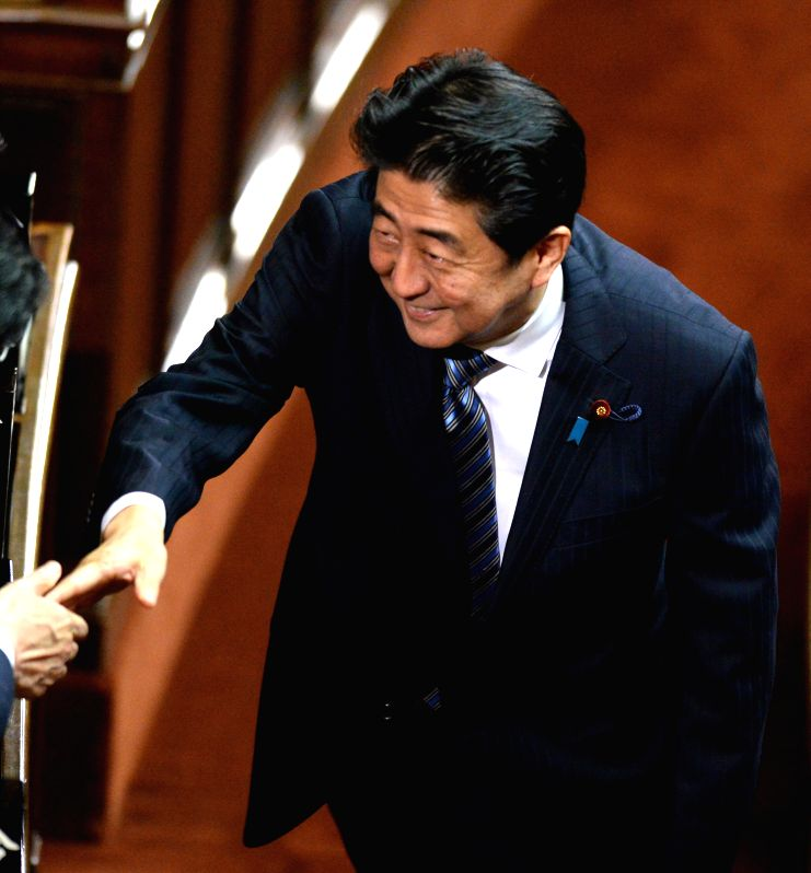 President of Japan's ruling Liberal Democratic Party (LDP) Shinzo Abe shakes hands with a colleague during the meeting at lower house in Tokyo, Japan, ...