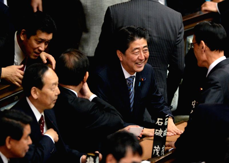 President of Japan's ruling Liberal Democratic Party (LDP) Shinzo Abe (C) talks with colleagues during the meeting at lower house in Tokyo, Japan, Dec. ...