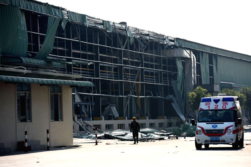 An ambulance waits outside the accident site after a gas blast rocked a plant of the Fuwa Engineering Manufacturing Co. Ltd. in the Shunde District of ...