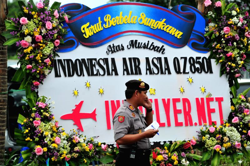 An Indonesian policeman walks past condolence sign for people on Indonesia AirAsia's flight QZ8501 at Juanda International Airport in Surabaya, ...