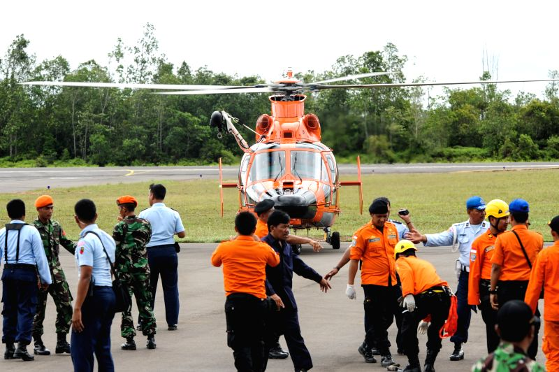 People gather around a helicopter that brings back bodies of victims on AirAsia flight QZ8501 at Iskandar Air Base, in Pangkalan Bun, Central ...