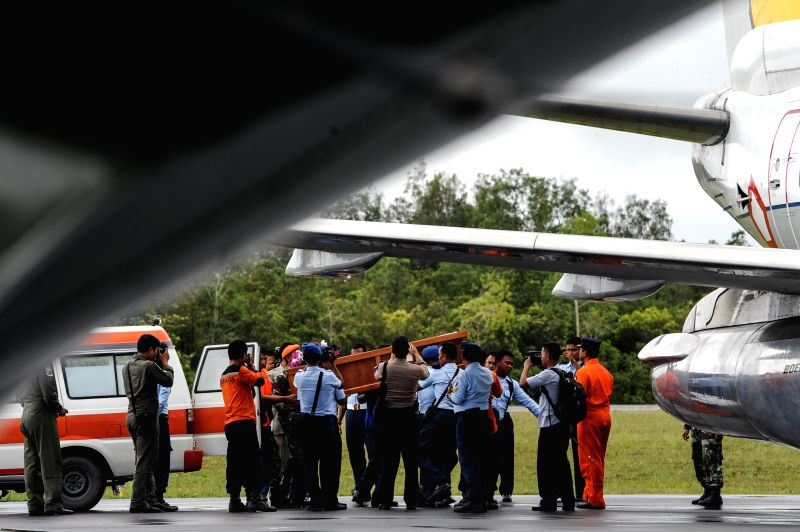 People carry the coffin containing victim of AirAsia flight QZ8501 to the Indonesia Air Bus Boeing aircraft at Iskandar Air Base, in Pangkalan ...