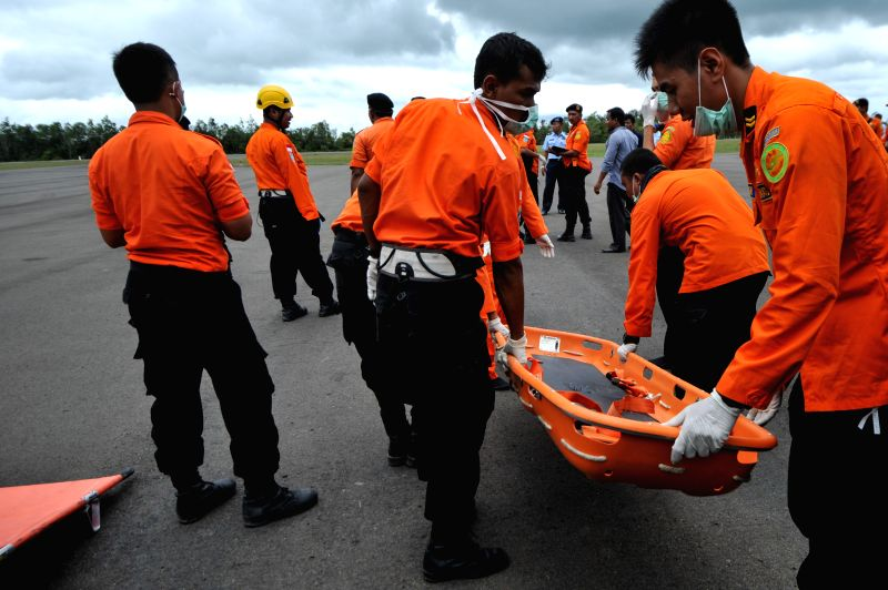 Search and Rescue (SAR) team members are ready to pick the retrieved bodies of victims on AirAsia flight QZ8501 at Iskandar Air Base, in Pangkalan