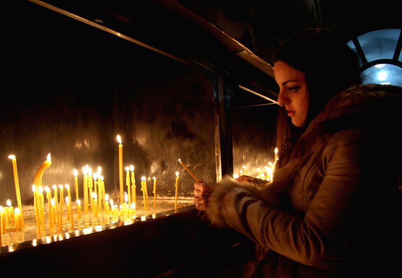 A girl lights candles in Banja Luka, northern Bosnia and Herzegovina, on Jan. 6, 2015. Orthodox Christians in central and eastern Europe and other ...