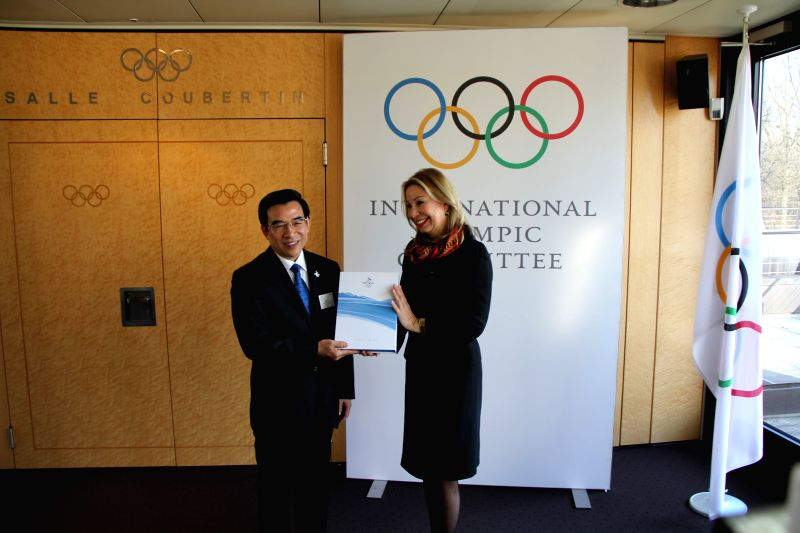 IOC head of Olympic bid city coordination Jacqueline Barrett (R) receives from the hands of Beijing 2022 Bid Committee president and mayor of Beijing ...