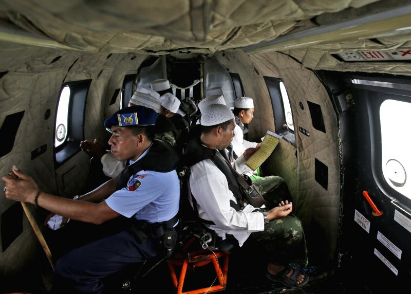 Muslim clerics perform a prayer for the victims of AirAsia QZ8501 inside an Indonesian Air Force NAS 332 Super Puma helicopter over the Java Sea ...