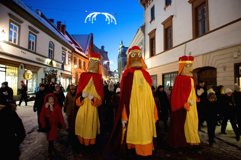 People parade through the streets during the celebration of Epiphany, a Christian festival commemorating Jesus' baptism in Jordan River, in Vilnius, ...