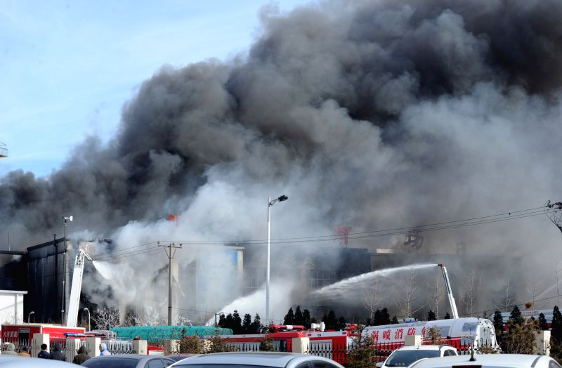 Smokes rise from a burning flea market in Dalian, northeast China's Liaoning Province, Jan. 7, 2015. A fire broke out on the market early on Saturday ...