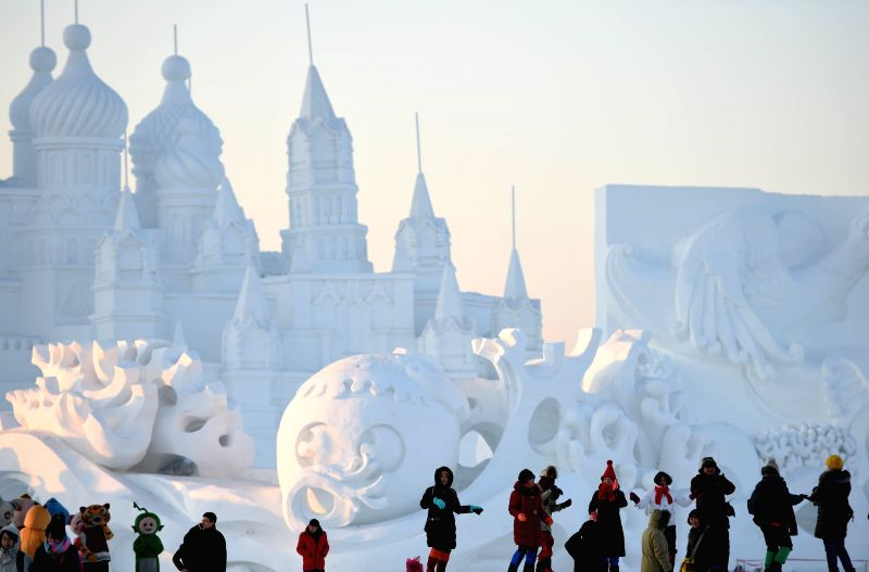 Tourists visit a snow sculpture at the 27th International Snow Sculpture Art Expo in Harbin, capital of northeast China's Heilongjiang Province, Jan. 6, ..