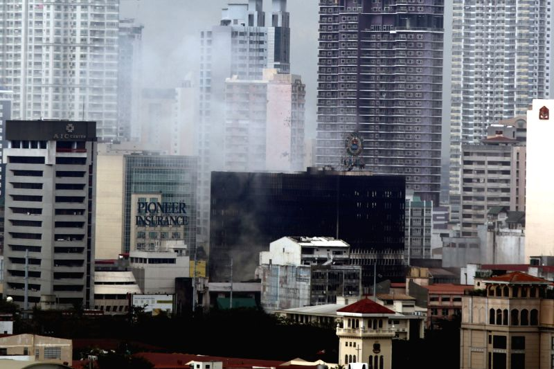 Smoke rises from a burning building in Manila, the Philippines, Jan. 7, 2015. An estimated 440,000 US dollars of damage was reported by the fire ...