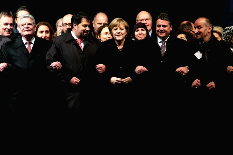 German Chancellor Angela Merkel (C, front) attends a vigil paying homage to the victims of French Charlie Hebdo attack and ensuing armed standoffs in ...