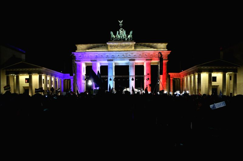 The Brandenburg Gate is lightened with the colors of French national flag during a vigil paying homage to the victims of French Charlie Hebdo attack and .