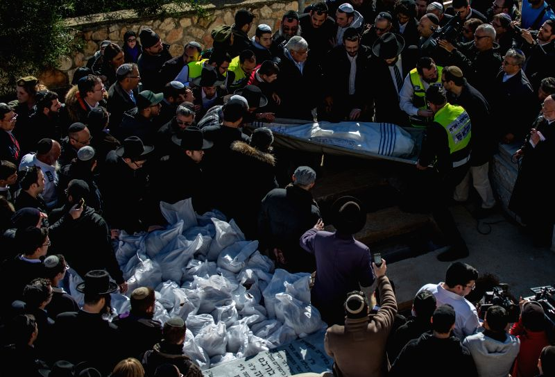 A body of victim of Paris supermarket attack is carried to the grave during a funeral ceremony at Givat Shaul cemetery, on the outskirts of Jerusalem,
