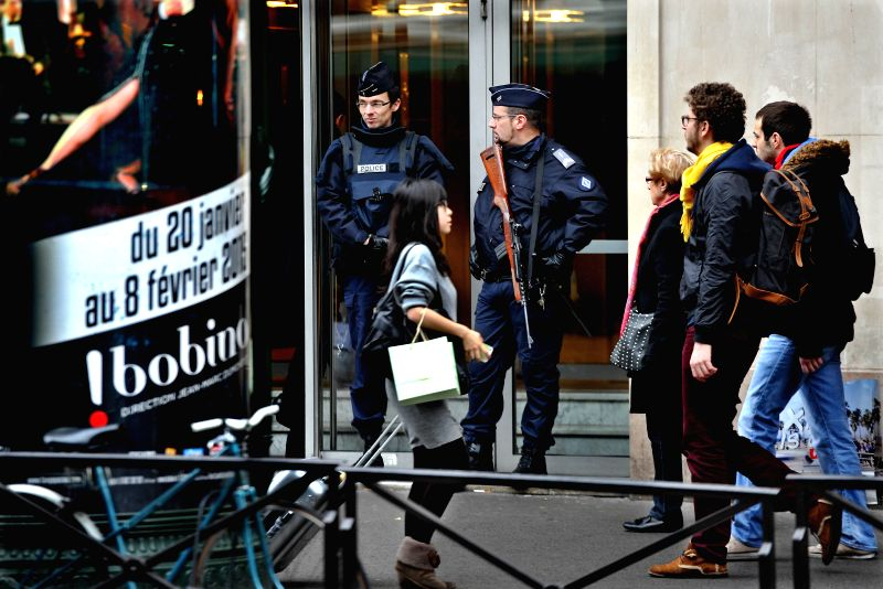 French armed policemen stand guard on a street in Paris, France, Jan. 13, 2015. Facing high risks of terror attacks, French government said 10,000 ...