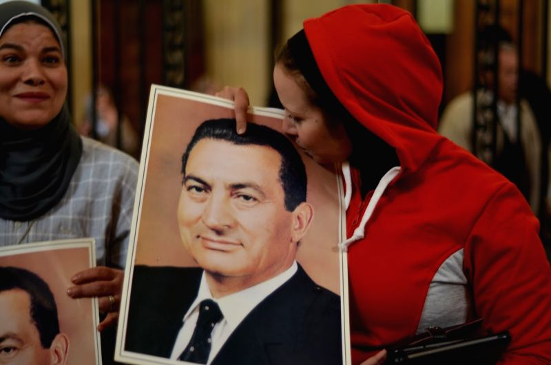 A supporter of ousted Egyptian President Hosni Mubarak kisses his portrait outside the court in Cairo, Egypt, on Jan. 13, 2014. Ousted Egyptian President .
